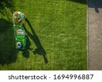 Caucasian Gardener Moving Lawn Aerial Photo.  Landscaping Business. Industrial Theme. - stock photo