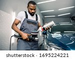 Small photo of African man, auto service worker, wearing white t-shirt and gray overalls, puts special wax or polish cream on the polishing machine to polish the car. Car detailing and polishing concept
