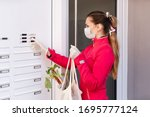 Small photo of Young woman helping neighbors by shopping groceries for people in covid-19 quarantine