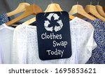 Small photo of Clothes Swap and recycle clothes icon on chalk board with hanging shirts to swap, sustainable fashion and zero waste, recycle clothes and textiles to reduce waste