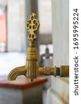 Small photo of Turkish Ottoman style antique ablution tap at the ablution fountain outside of Fatih Mosque, Istanbul, Turkey, includes clipping path