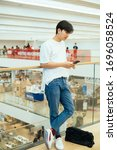 Small photo of Teenage guy in jeans and white t-shirt leaning against the glasses barricade while standing with smartphone on the mezzanine.