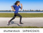 Small photo of A profile young girl focused driven running with a sharp, intense body language at the waterfront park. She is staying on track while training for a competitive sport is essential to winning.