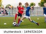 Small photo of Kids Football Players Kicking Ball on Soccer Field. Sports Soccer Horizontal Background. Spectators on Stadium in the Background. Youth Junior Athletes in Red and Blue Soccer Shirts. Sports Education