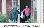 An elderly woman with a walker who is at high risk because of the coronavirus COVID19 gets meals or groceries delivered to her house by a volunteer working with a benevolent organization.