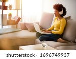Small photo of Young afro-american Woman drinking water and surfing the net on the sofa at home. Young woman working from home office. Freelancer using laptop, phone and the Internet. Workplace in living room