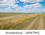 view of rural locality with a river and clouds in the background - stock photo