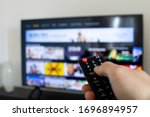 Small photo of Tv remote controller in hand of customer looking for some content in Smart Tv app for streaming video. Watching streaming services for entertainment on television. Choosing TV series and movies
