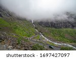 Winding Road Serpentine road in the mountains of Norway, gloomy weather, wet asphalt, selective focus - stock photo