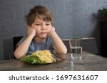 Small photo of The child doesn't want to eat. The boy eats spaghetti. Poor appetite. Healthy diet. Refuses to eat. A disgruntled child at lunch.