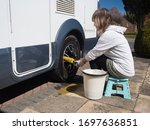 A lady motorhome owner cleans the wheels of her recreational vehicle with a yellow wheel brush.She has a bucket beside her as she sits on a stool.Image - stock photo
