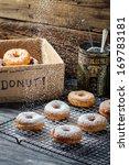 Closeup of falling icing sugar on fresh donuts - stock photo