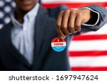 Small photo of Unrecognizable african citizen of America holds I voted today button, typical of US elections on American flag.