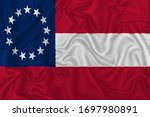 Confederate States of America flag (1861-1865) on wavy silk textile fabric background.