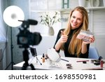 Small photo of Beauty blogger woman filming daily make-up routine tutorial near camera. Influencer girl live streaming cosmetics product review. Vlogger female recommends eye shadow palette showing thump up sign.