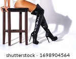 Girl sitting on a chair made of wood dark brown. Black hessian boots on the feet of a model on a white background with shadows. jackboots. studio shooting. thin legs. fashionable boots. - stock photo