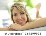 smiling blond woman relaxing in ... | Shutterstock . vector #169899935