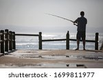 Fisherman Fishing Off A Pier On ...