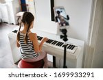Small photo of Girl child plays the digital piano and records video on the phone, online learning and video chat on learning to play the piano, remote music lessons online. Authentic lifestyle in a real interior