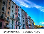 Rows of colorful apartments spread across the Porto Venere town against a blue summer sky. Photo taken on 28th of September 2016 in the small town of Porto Venere on the Ligurian coast of Italy. - stock photo