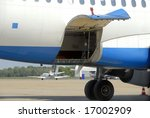 Open hydraulically operated cargo compartment door of an airplane at the airport - stock photo