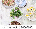 Overhead of a variety assortment of side dishes, green salad, brown rice salad, lentil beetroot salad on a rustic background with copy space - stock photo