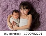 Little Sister Hugs Her Newborn...