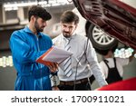 Small photo of Car service, vehicle repair concept : Car service technician explaining checking list or repaired item to vehicle owner customer after sending car for repairing or check at automobile service center.