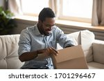 Small photo of Excited biracial young man sit on couch at home unpack cardboard box with Internet order, happy African American male open carton package at home, shopping on web, good delivery service concept