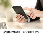 Small photo of Cloe up of executive woman hands checking smart phone sitting on a desk at office