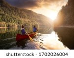 Couple friends canoeing on a wooden canoe during a colorful sunny sunset. Cloudy Sky Composite. Taken in Harrison River, East of Vancouver, British Columbia, Canada.