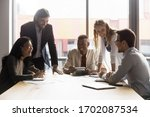 Small photo of Excited diverse coworkers sit at office desk laugh have fun discussing paperwork at meeting together, overjoyed businesspeople gather at table in boardroom joke smile brainstorming at meeting