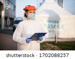 Small photo of Paramedic wearing personal protective equipment PPE holding folder standing in front of ICU hospital isolation rt-PCR drive thru testing site,COVID-19 pandemic outbreak crisis,worried exhausted staff
