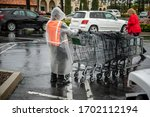 Small photo of Essential worker at grocery store in rain coat collecting shopping carts in the rain