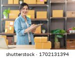 Small photo of Young attractive asian woman owner startup business look at camera work happy with box at home prepare parcel delivery in sme supply chain, procurement, omnichannel or coronavirus quarantine concept.