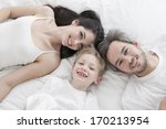 lovely family lying in bed | Shutterstock . vector #170213954