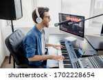 Man plays guitar and singing and produce electronic soundtrack or track in project at home. Male music arranger composing song on midi piano and audio equipment in digital recording studio - stock photo