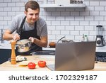 Small photo of Young man wearing black apron in the modern kitchen looking for recipes on his laptop. Cooking in home, online recipe, remote cooking classes