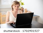 a woman in home clothes works... | Shutterstock . vector #1702901527