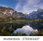 Autumn evening alpine view. Peaceful mountain lake with clear transparent water and reflections.  Almsee lake, Upper Austria. - stock photo
