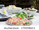 Garden summer party buffet style with different salads on the table, green leafy, brown rice pilaf with cherry tomatoes - stock photo