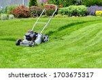 A Lawn Mower On A Lush Green...