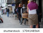 Small photo of Low angle and selected focus, European people queue and wait for shopping on sidewalk outside supermarket during quarantine for COVID-19 virus in Dusseldorf, Germany.