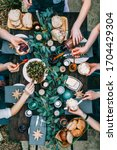 Small photo of Top view over a dining table, decorated with eucalyptus leaves, with tableware and food. Backyard picnic with friends or neighbors.