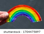 Small photo of fingers hold paper watercolor rainbow on dark background, symbol of positive and happiness, sign of the colors of life, symbol of the covenant