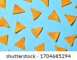 Small photo of Nachos Mexican chips colorful pattern on blue background. Tortilla nacho chip closeup, fashionable trendy flat lay. Crisps nachos snack wallpaper, top view. Creative concept
