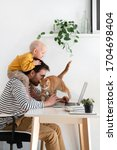 Small photo of Working from home. Father freelancer with baby and cat in home office at his desk. Family indoors