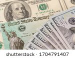 Small photo of Stack of 100 dollar bills with illustrative coronavirus stimulus payment check to show the virus stimulus payment to Americans