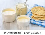 Small photo of Sweet Condensed or evaporated milk and waffles on a table. A delicious Breakfast.