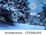 City Park with snowy fir trees and benches, can be seen the dome at night - stock photo